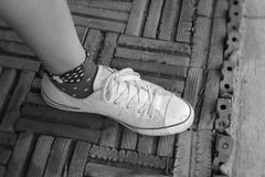 Legs with wore white sneakers. Royalty Free Stock Photo