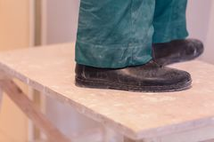 Legs of worker with green workwear and black shoes on the wooden stepladder. Worker makes plasterboard drywall for. Gypsum walls in apartment is under Royalty Free Stock Photos