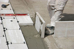Legs of worker laying tiles. Legs of worker laying large tiles outdoors Stock Photos