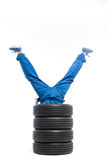 Legs of the worker stick out of the pile of tires. Tyre service, legs of the worker stick out of the pile of tires, white background, repairman, wheel mounting Stock Image