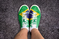 Legs wth sport shoes colored the brazilian flag Stock Photos