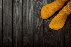 Legs yellow knitted woolen socks on wooden dark background. Royalty Free Stock Photos