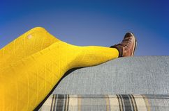 Yellow Tights Sofa. Legs in Yellow Tights resting on Outdoor Patterned Sofa, against the blue sky Royalty Free Stock Photo