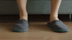 Legs of young adult man in a slippers - feet level Stock Images