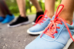 Legs of young athletes prepared for run in green sunny park. Royalty Free Stock Photography