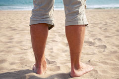 Legs of Young Caucasian man on sandy beach Royalty Free Stock Photo