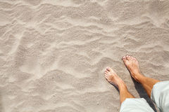 Legs of Young Caucasian man standing on sandy beach Royalty Free Stock Photos