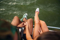 Legs of young couple in sneakers sitting near the sea. Top view of legs of young couple in sneakers sitting near the sea Royalty Free Stock Photos