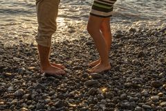 Legs of a young couple standing at the seaside, at nice sunset stock photography