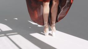 Legs of young dancers, class of ballet. Ballet dancer in a red skirt. Movement with the foot. Pointe shoes. Slow Motion stock video