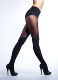 Legs of a young and fit woman in black stockings Royalty Free Stock Photography