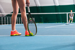 Legs of young girl in a closed tennis court with ball and racket Royalty Free Stock Photos