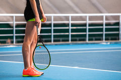 Legs of young girl in a closed tennis court with ball and racket Stock Image