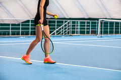 Legs of young girl in a closed tennis court with ball and racket Royalty Free Stock Photography
