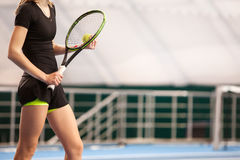 Legs of young girl in a closed tennis court with ball and racket Stock Photo