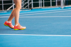 Legs of young girl in a closed tennis court with ball and racket Royalty Free Stock Image