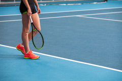 Legs of young girl in a closed tennis court with ball and racket Stock Photos