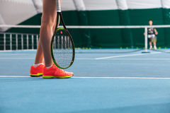 Legs of young girl in a closed tennis court with ball and racket Royalty Free Stock Photo