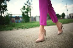 legs of a young girl in heels in step  on grass background royalty free stock image