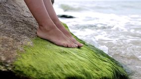 Legs of a young girl on a stone near the sea stock footage