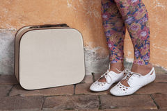 Legs of the young girl in white shoes. Legs of the young girl in white shoes next to a suitcase Stock Image
