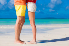 Legs of young hugging couple on tropical turquoise beach Royalty Free Stock Image