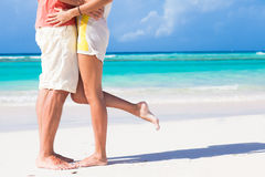 Legs of young hugging couple on tropical turquoise Stock Image