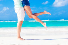 Legs of young kissing couple on tropical turquoise Stock Photos