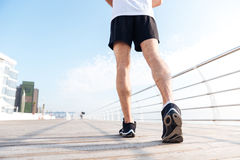 Legs of young man in black sneakers running on pier Stock Photos