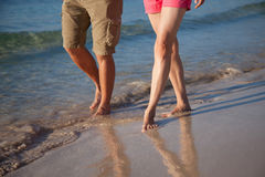 Legs of a young man and woman walking along near the sea Royalty Free Stock Photos