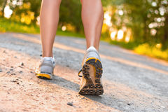 Legs of young sport woman walking on the road Royalty Free Stock Images