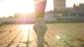 Legs of young woman ballerina standing on the roof on her tiptoes - sunset