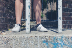 Legs of young woman by bars Stock Photos
