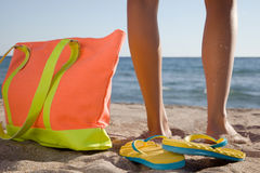 Legs of the young woman on the beach. With the beach bag Stock Photos
