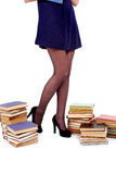 Legs of young woman with books isolated on white. Young woman with books pile isolated on white Royalty Free Stock Photo