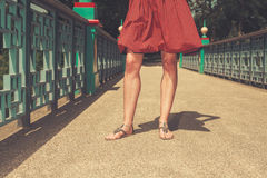 The legs of a young woman on a bridge Stock Images