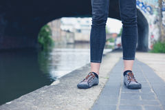Legs of young woman by canal Stock Photography