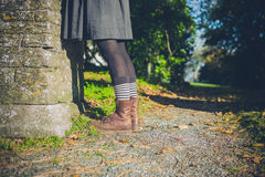 Legs of young woman in the countryside by wall Royalty Free Stock Photos