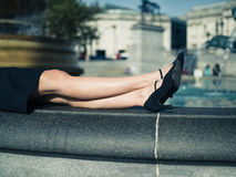 The legs of a young woman by fountain in city Royalty Free Stock Image