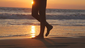 Legs of young woman going along ocean beach during sunrise. Female feet walking barefoot on sea shore at sunset. Girl stock video footage
