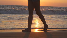 Legs of young woman going along ocean beach during sunrise. Female feet walking barefoot on sea shore at sunset. Girl Royalty Free Stock Photography