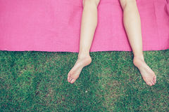 The legs of a young woman on the grass Stock Images