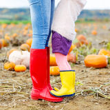 Legs of young woman and her little girl daugher in rainboots. Royalty Free Stock Photos