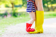 Legs of young woman and her little girl daugher in rainboots Royalty Free Stock Image