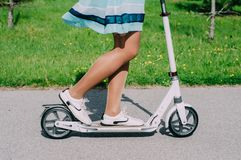 Legs of young woman on kick scooter. Legs of young woman in dress on kick scooter Royalty Free Stock Photography