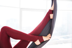 Legs of young woman in leggins using hammock at studio Royalty Free Stock Images