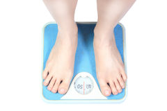 Bare female feet standing on bathroom scale. Legs of a young woman measuring her weight on a bathroom scale royalty free stock photos