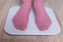 Legs of a young woman measuring her weight on a modern smart scales stock photo