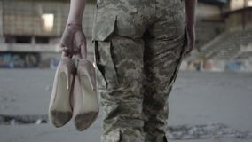 Legs of young woman in military uniform walking slowly in dusty dirty abandoned building carrying high-heeled shoes in. Legs of a young woman in military uniform stock footage
