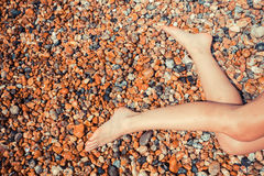 Legs of a young woman on a pebble beach Royalty Free Stock Photo